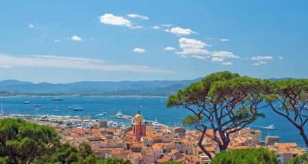 세인트 트로 페 즈 (S Tropez)의 고상한 장소에서 만든 이미지. 집의 빨간 지붕과 푸른 하늘이 산의 지평선에서 멀리 떨어져 있습니다. 스톡 콘텐츠