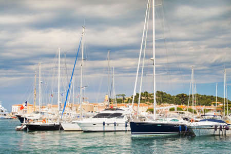 tropez: Beautiful image of yachts against the backdrop of the city of St. Tropez in France. Interesting lighting accentuates the beauty of clouds azure shores.