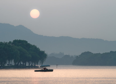 tele: Tele image of Xihu Lake at sunset, Hangzhou, China, Asia. Young couple is boating by boat.