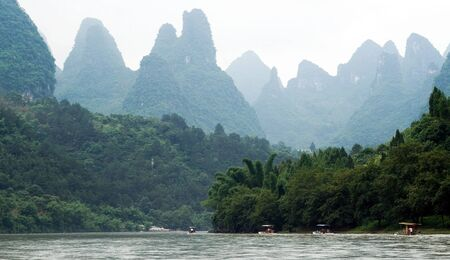 punting: Traveling people through valley of Li River between Yangshuo and Xing Ping village with amazing view at the mountain range