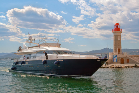 palate: The image of the yacht, passing by the lighthouse of San Tropez. On the palate beautifully illuminated clouds. Editorial
