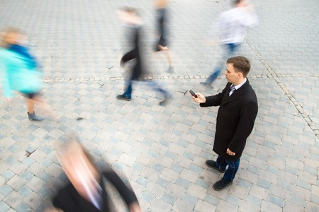 busy street: Young attractive businessman talking on mobile phone. Motion blurred commuters walking to work