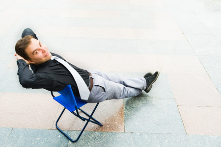 Image of the businessman sitting andrelaxing in the empty street. Focus is made on top of the background marbled tile in the street.