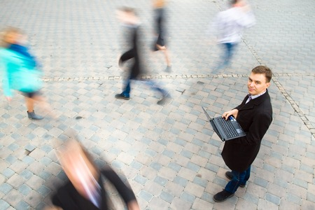 wireless technology: Young attractive businessman working on laptop through wireless technology. Motion blurred commuters walking to work Stock Photo