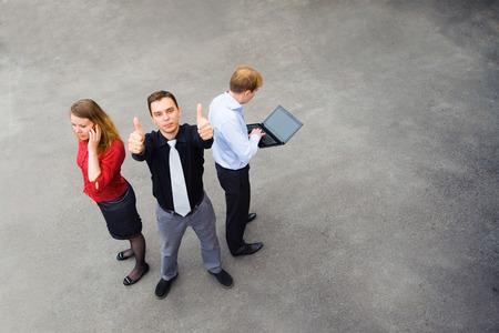 Beeld van het bedrijfsleven team van 3 personen. Aandacht gegeven bovenop de grijze achtergrond van de lege straat.