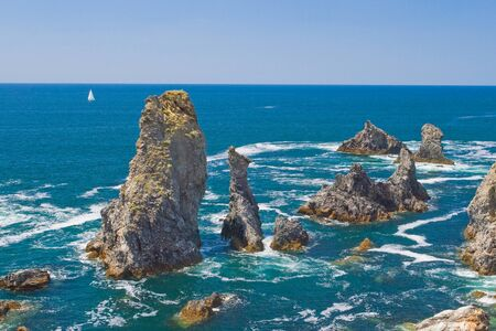 ünlü yer: The image of the famous places on the island Belle Ile en Mer - Aiguilles de Port-Coton with the waves pounding on the rocks, each of which has its name from its shape. Stok Fotoğraf