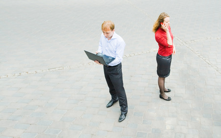 purposeful: Image of the business partners using communication and standing on the street. They have absolutely thoughtful and purposeful face.