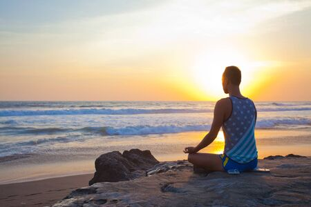 yoga outside: sitting man doing yoga on shore of ocean, bali, indonesia Stock Photo