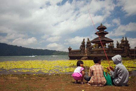 bratan: Image of the main water temple Ulun Danau Bali on Bratan Lake. Front of the temple children of three sitting and go fishing together. Indonesia. Editorial