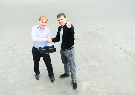 concluding: Image of the business partners concluding a bargain and standing on the street. Stock Photo