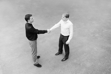 concluding: Black and white image of the business partners concluding a bargain. Focus is made on top of the gray background of the empty street.