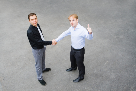 concluding: Image of the business partners concluding a bargain. Focus is made on top of the gray background of the empty street. Stock Photo