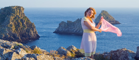 resisting: Picture of a beautiful girl with pink shawl, resisting strong winds on the cape Pen Hir at sunset, France.