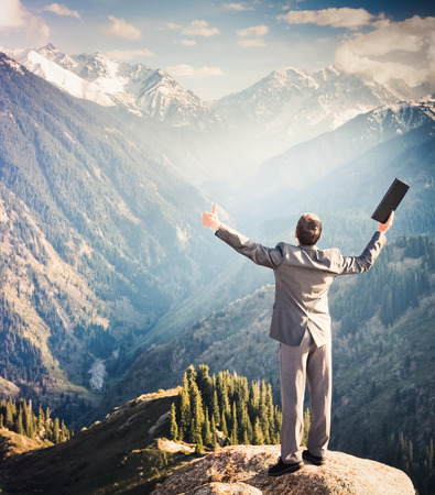 successes: Image of a young businessman with laptop standing at the top of the mountain and looking into the distance to the beautiful mountains, is pleased with the achieved successes. Stock Photo
