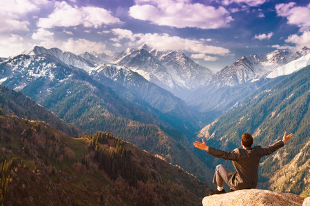 successes: Image of a young businessman who sits on the top of the mountain on the background of the beautiful mountains, relaxing and pleased with the achieved successes. Stock Photo
