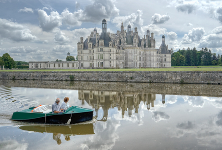 chambord: Old couple grandmother and grandfather travel together by boat in Loire, France. Castle Chambord, Leonardo da Vinci. They are together a many long years.