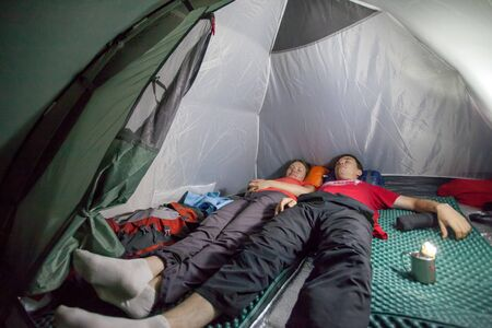 camping tent: Image of sleeping tourists inside the tent camp on the background of night lighting flashlight in Almaty, Kazakhstan