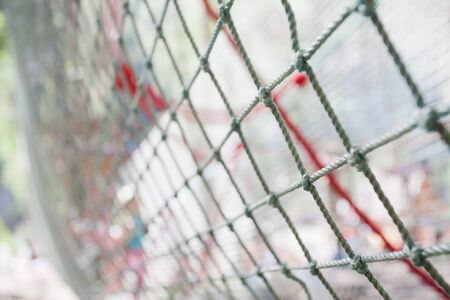 lengthy: background of rope net in the childrens rope park in the forest. Focus on foreground.