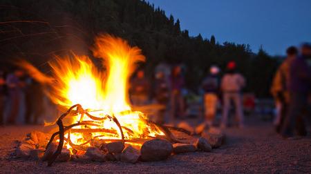 사람들이 밤에 산에서 햇볕을 쬐고있는 주위에 큰 모닥불의 이미지
