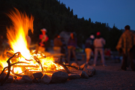 Image of a large campfire, around which people basking in the mountains at night 스톡 콘텐츠