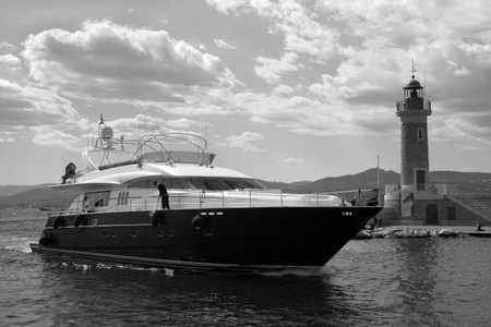 palate: Black and white image of the yacht, passing by the lighthouse of San Tropez. On the palate beautifully illuminated clouds.