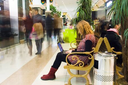 wireless technology: Young attractive woman working on laptop in the mall and using wireless technology. Motion blurred crowd (people) Stock Photo