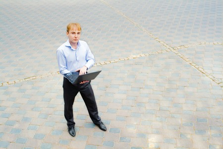 purposeful: Image of a businessman using his laptop and standing on the street. On the face of a businessman thoughtful and purposeful look. Editorial