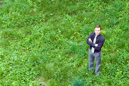 contented: Image of a contented businessman looking in the camera and standing on the grass in the nature. Stock Photo