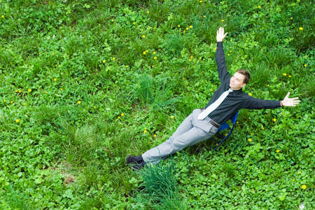contented: Image of a contented businessman sitting on the grass in the nature. The sign of success raised a hand up.