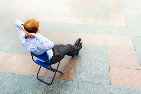 debility: Image of the businessman sitting andrelaxing in the empty street. Focus is made on top of the background marbled tile in the street.