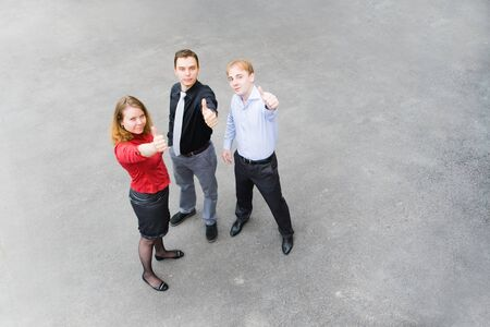 success focus: Image of business team of 3 people who raised their hands as a sign of success. Focus is made on top of the gray background of the empty street. Stock Photo