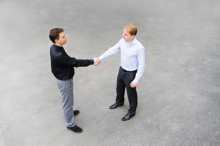 concluding: The image of the business partners concluding a bargain. Focus is made on top of the gray background of the empty street. Stock Photo