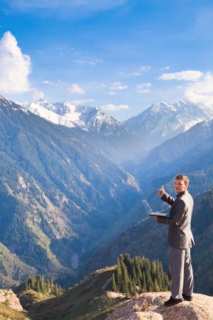 successes: Immagine di un giovane uomo d'affari con il laptop in piedi in cima alla montagna e guardando in lontananza alle belle montagne, � soddisfatto dei successi ottenuti.