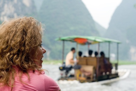 portret: Portret image of young smiling women traveling by boat on the river in China, Yangshuo Stock Photo