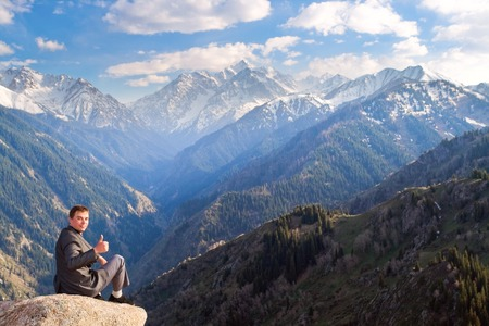successes: Image of a young businessman who sits on the top of the mountain and looks at the camera on the background of the beautiful mountains, pleased with the achieved successes. Stock Photo