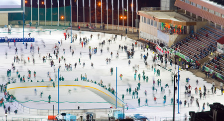 skating rink: Huge ice skating rink whith motion blurred large group of skating people. Kazakhstan, Medeo is an outdoor speed skating and bandy rink, located in a mountain valley