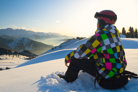 freeride: An image with sitting snowboarder with a helmet and glasses on the background of high snow-capped Alps in Austria