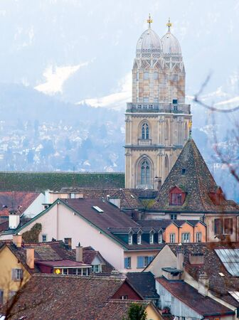 lit image: Image of two high towers with color roofs of the old houses and Cathedral. On the background the snowy Alps, lit sunset light, Zurich. Stock Photo