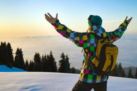 climbed: Image of a young sportsman, who climbed to the snowy mountains to meet the sunset. In the background clouds, illuminated by all shades of the sunset after a bright sunny winter day.