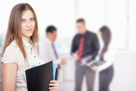 achieve: Successful business woman at foreground and business team of men and woman at background. Image symbolizes a successful corporation or company where achieve success for intelligent and beautiful women