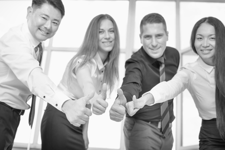 far off: Multiracial successful business people and team with thumbs up gesture. They did it! Success is not far off! Stock Photo