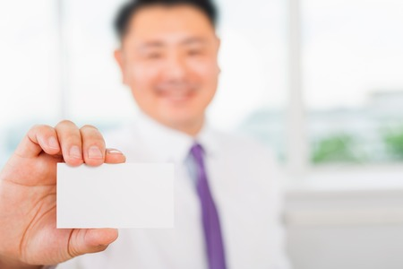 happy asian people: Happy and successful asian businessman gives you a business card or visiting card with a white background on a blank for copy space and any contacts or phone number Stock Photo