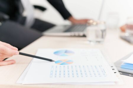 financial reports: close-up graph and charts on the table during business meeting at office. Officer reports about financial achievements for a seminar Stock Photo