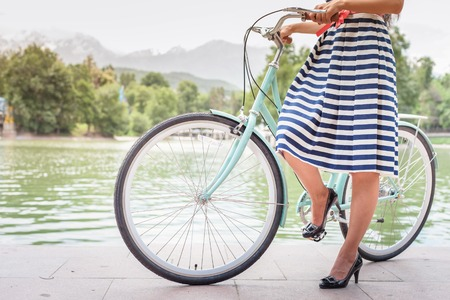 retro vintage: closeup image of beautiful woman dressed in fashion dress travel by vintage city bicycle at summer time near the lake or pond at park Stock Photo