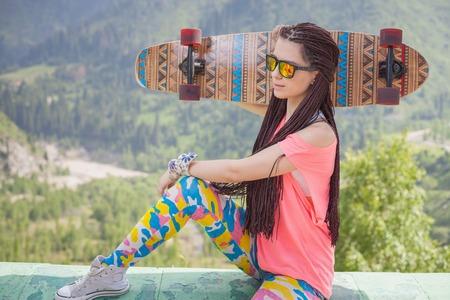 mujer hippie: Chica joven y hermosa del Hippie con la patineta al aire libre en la montaña. Longboard es la cultura más popular y peligroso juventud
