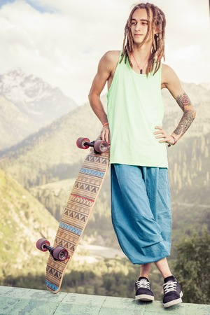 youth culture: Hippie young and handsome man with skateboard outdoor at mountain. Longboard is the most popular and dangerous youth culture Stock Photo