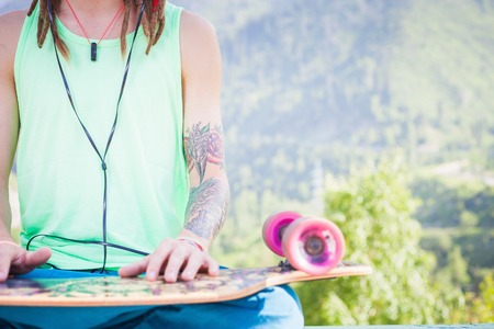 oncept: Closeup Hipster relaxing and handsome man listening to music with skateboard outdoor at mountain. ?oncept of meditation on a background of nature