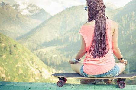 ライフスタイル: 流行に敏感なファッションの女の子ヨガ、リラックス、山にあるスケート ボードの上に座ってのクローズ アップ画像。