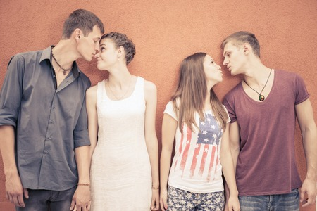 international flags: Small group of young people kissing and standing in row near red wall background.  Stock Photo