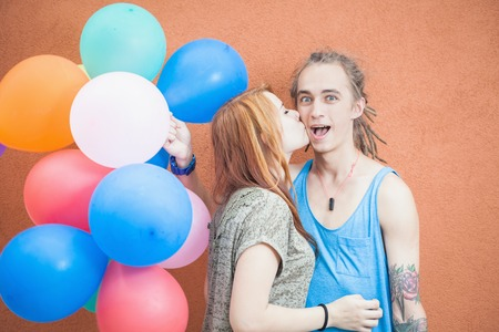young couple hugging kissing: Young happy couple near the orange wall stand with balloons. The girl kisses the young mans cheek. Man smiling enthusiastically
